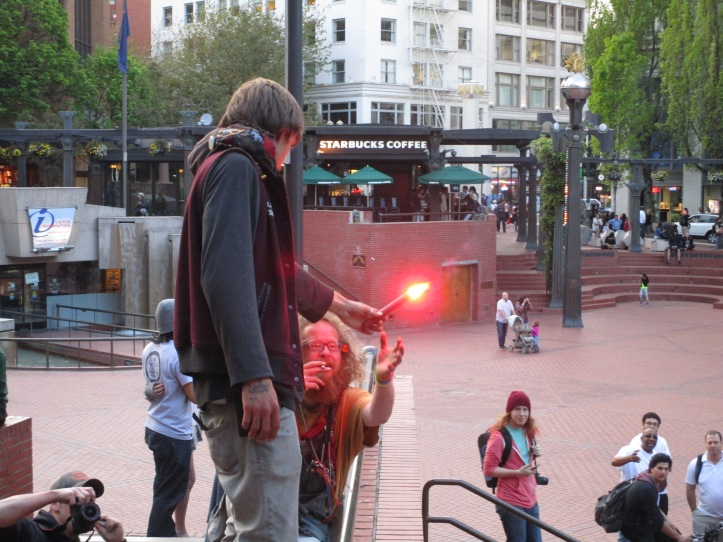 A protester with a flare lights another protester's cigarette at the Pioneer Courthouse Square, where some protesters congregated after disbanding the march. Jaime Dunkle/PSU Vanguard